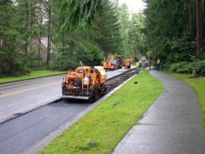 A Puget Sound Energy contractor is in the process of replacing the temporary cold-patch on Village Green Drive with a permanent hot-patch that will be much smoother and more drivable.