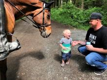 Little boy and Dad meet horse. Photo credit: Joan Deutsch.