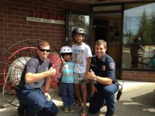 Mill Creek Firefighters Randy Mickels and Michael McConnell (left to right) helped fit more than 75 children with low or no cost bicycle helmets during Fire District 7's first Summer of Safety event. Photo courtesy of Fire District 7.